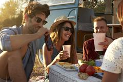 Friends on a road trip having a picnic beside a camper van Stock Photos