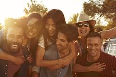 Three couples having fun piggybacking at sundown Stock Photos