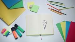 Girl writing word idea on notepad above lightbulb Stock Footage