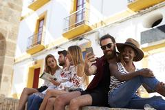 Friends sit on wall reading a guidebook and taking selfies Stock Photos