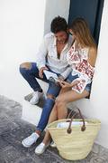 Young couple sitting on steps looking at a guidebook, Ibiza Stock Photos