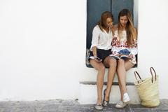 Female friends sitting in doorway reading a guidebook, Ibiza Stock Photos