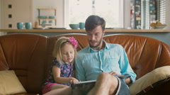 Blond little girl is choosing a story that her loving father will read on the Stock Footage