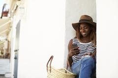 Young woman on holiday sitting on steps looking at phone Stock Photos
