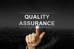 Business hand pushing quality assurance button on black blurred background Stock Photos