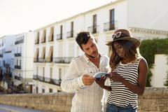 Young couple reading a guidebook, waist up, Ibiza, Spain Stock Photos