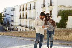 Young couple reading a guidebook in the street, Ibiza, Spain Stock Photos