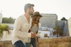 Young adult couple sightseeing in Ibiza, Spain, side view Stock Photos