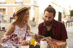 Couple sit reading guidebook outside a cafe, Ibiza, Spain Stock Photos