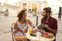 Laughing couple reading a guidebook outside a cafe in Ibiza Stock Photos