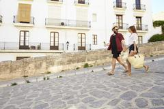 Couple on holiday walking with guidebook, holding hands Stock Photos