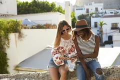 Two female friends sitting on wall reading guidebook, Ibiza Stock Photos