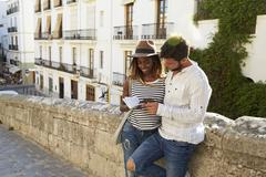 Couple leaning against a wall reading a guidebook, Ibiza Stock Photos