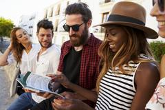 Friends on vacation in Ibiza looking at a guidebook, close up Stock Photos