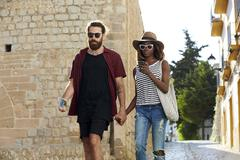 Couple on holiday walk, looking at phone, Ibiza, Spain Stock Photos