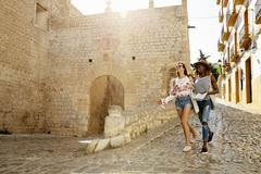 Two female friends on holiday walking with guidebook, Ibiza Stock Photos