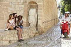 Couple on scooter ride past friends sitting on a wall, Ibiza Stock Photos