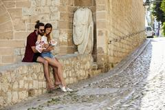 Man embracing his girlfriend on a wall, reading a guidebook Stock Photos