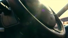 Man putting his hands on leather steering wheel against blazing sun, warm colors Stock Footage