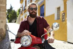 Bearded young man sitting on motor scooter, Ibiza, Spain Stock Photos