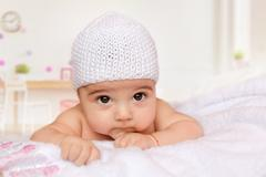 Little baby lying on his stomach in a white knitted cap Stock Photos