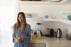 Young woman standing in kitchen holding cup, waist up, Ibiza Stock Photos