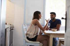 Young adult couple sitting in kitchen smiling, drinking wine Stock Photos