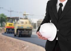 Engineer in suit holding helmet with asphalt road under construction Stock Photos