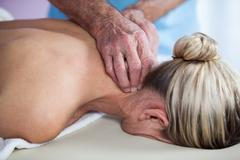 Woman receiving neck massage from physiotherapist Stock Photos