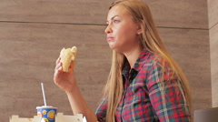 Beautiful girl eating fast food Stock Footage
