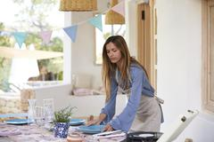 Young woman preparing table on a terrace for a dinner party Stock Photos