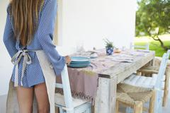 Back view of woman preparing table outdoors for dinner, crop Stock Photos