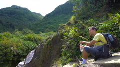 Man drinking water sitting on cliff. Break in hiking Stock Footage