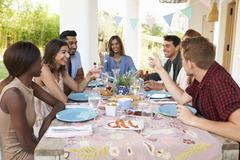 Adult friends at a dinner party on a patio, guest's view Stock Photos