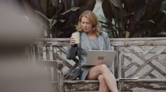 Attractive businesswoman on laptop computer on a bench outside Stock Footage