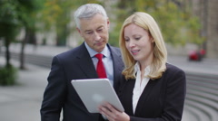 Professional businessman and businesswoman look at tablet and discuss content Stock Footage