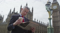 Businessman reading the newspaper in the city of London Stock Footage