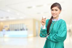 Female doctor wearing a green scrubs and stethoscope in hospital Stock Photos