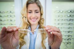 Smiling female optometrist holding spectacles Stock Photos