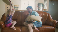 A young father and his cute happy little daughter having pillow fight on the Stock Footage