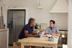 Dad and son using technology eat and talk at kitchen table Stock Photos
