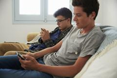 Two teenage boys relax, messaging friends with smartphones Stock Photos