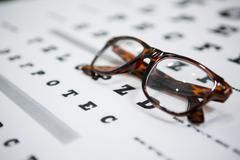 Close-up of spectacles on eye chart Stock Photos