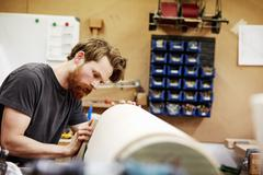 A man working on a curved wooden piece. Stock Photos