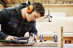 A young man using tools to shape a piece of wood. Stock Photos