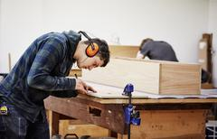 A man marking a piece of wood with a pencil. Stock Photos