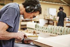 A man using a small handsaw to trim wood. Stock Photos