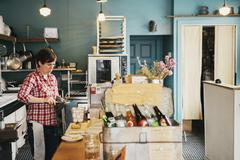 A woman working behind the counter, Business owner. Stock Photos