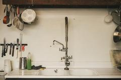 The sink and taps, a knife rack and equipment hanging from tea beam. Stock Photos