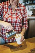A woman working in a small commercial kitchen, a coffee shop owner. Stock Photos